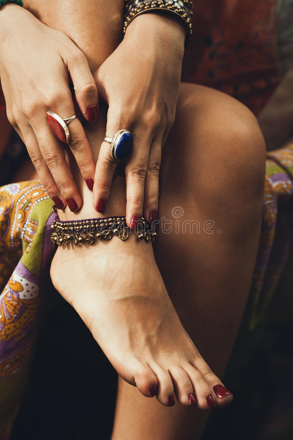 Female hand and feet summer boho jewelry. Closeup of female hand and feet boho summer jewelry outdoor shot, rings and ankle bracelet royalty free stock photos