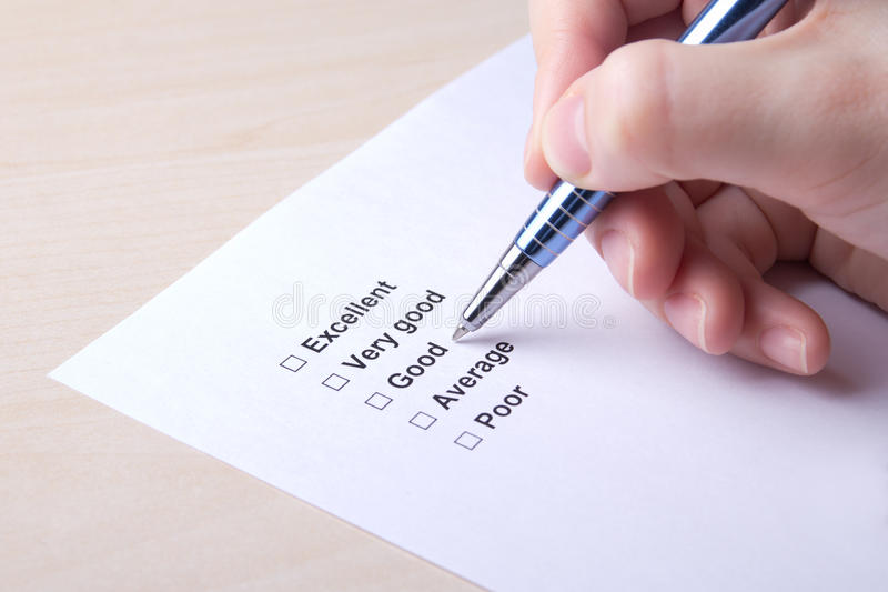 Female hand filling customer survey with pen royalty free stock images