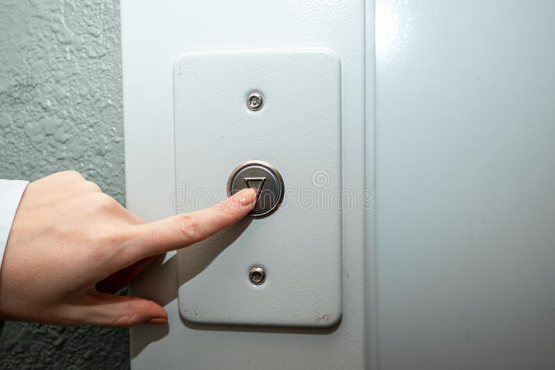 Female hand, finger presses the elevator button. up the career ladder royalty free stock photo