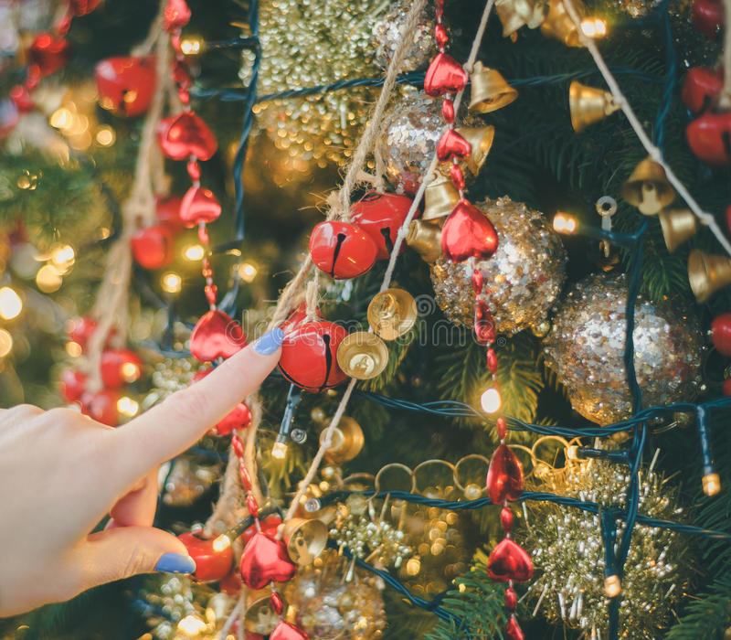 Female hand finger touching holiday ornaments. On Christmas tree stock photography