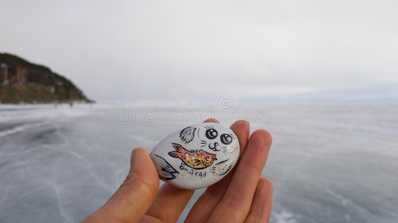 Female hand fingers holding a small decorative magnet with the inscription in Cyrillic `Baikal`. Souvenir from Siberia. On the background of mountains and ice stock illustration