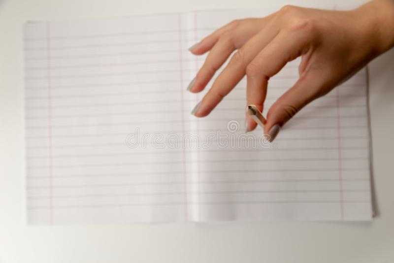 Female hand fingers are keeping yellow pencil on the notebook in a ruler with fields. International Students Day. stock image