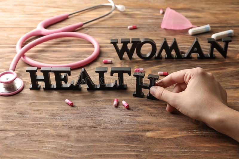 Female hand forming text WOMAN HEALTH on wooden table stock photos