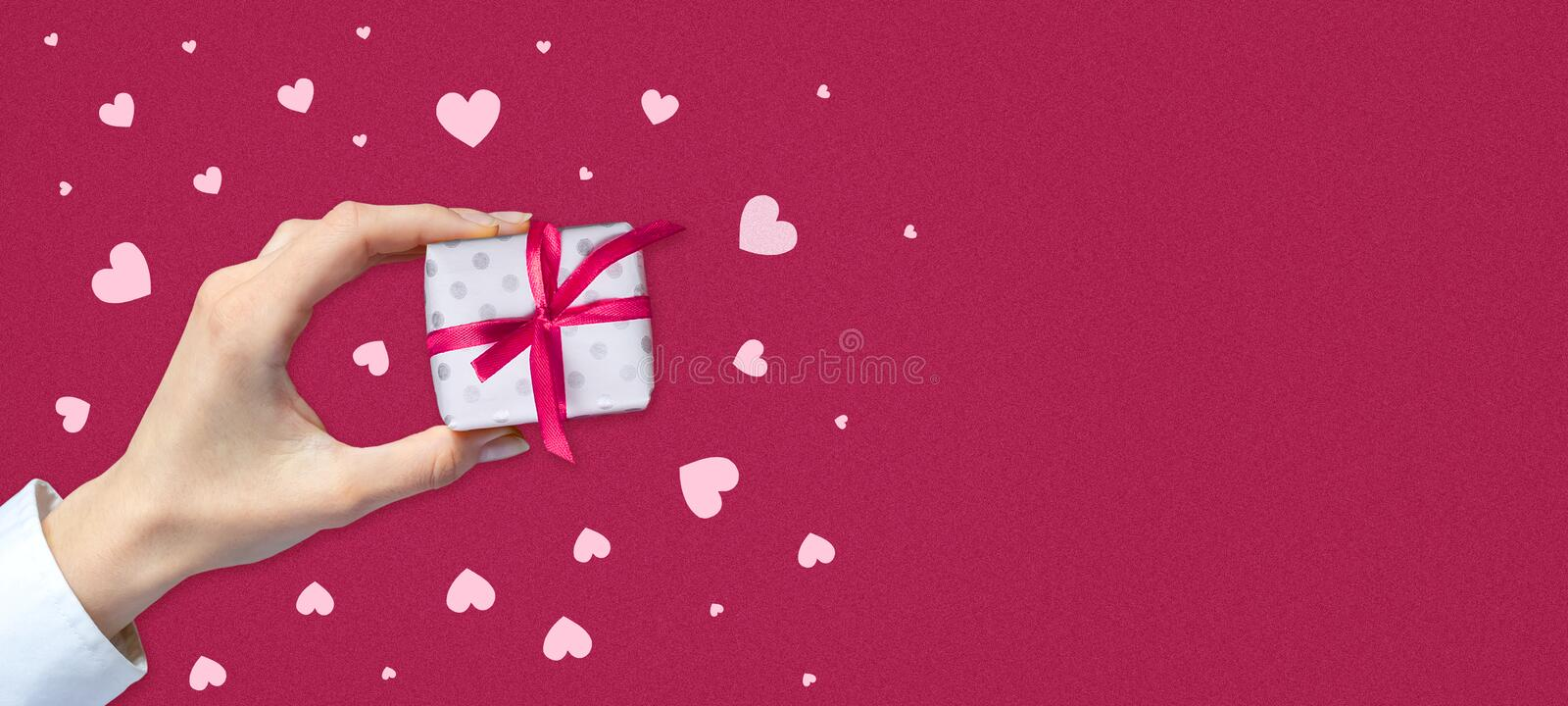 Female hand with a gift on a pink background with hearts. Copy space. Place for text. Mothers Day. St. Valentine`s Day. Birthday. Greeting card. Festive banner royalty free stock photos