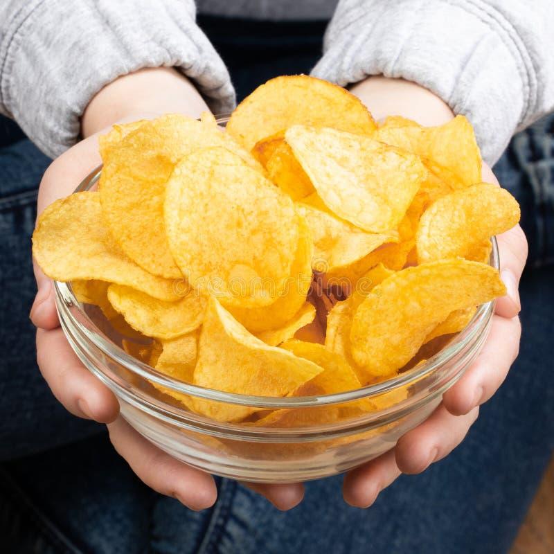 Female hand giving crispy potato chips bowl stock photography