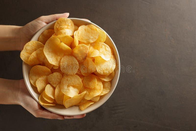 Female hand giving crispy potato chips bowl. royalty free stock photos