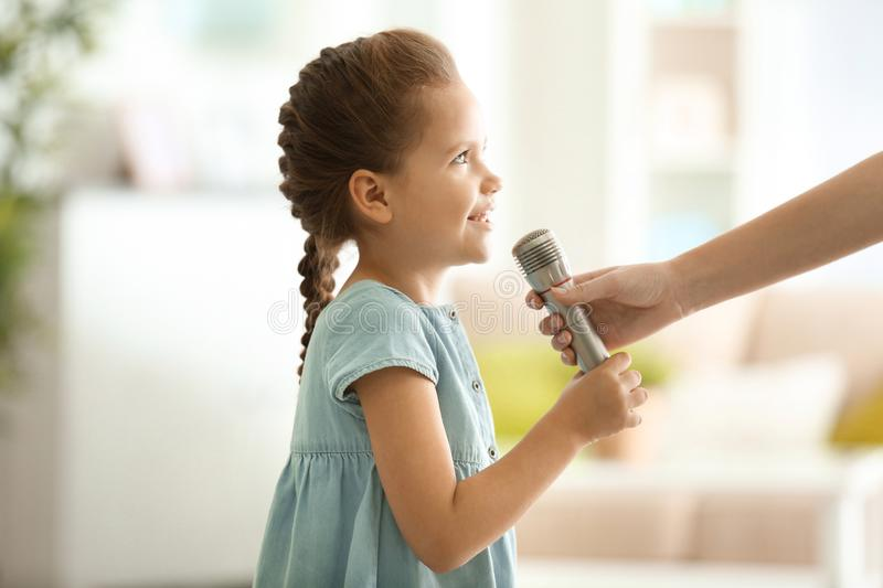 Female hand giving microphone to cute little girl at home stock image