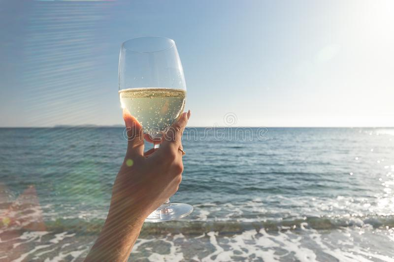 Female hand with glass of wine on the beach. Summer vacations concept royalty free stock photography