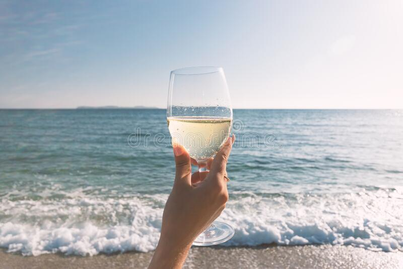 Female hand with glass of wine on the beach. Summer vacations concept stock photography
