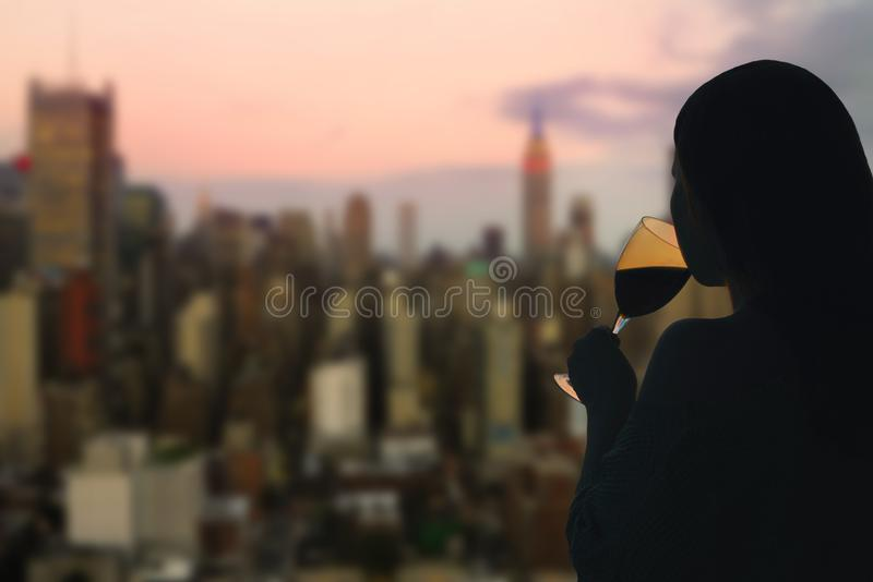 Female hand with glass of wine on Manhattan background. New York city. royalty free stock photography