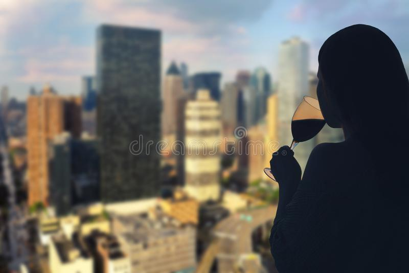Female hand with glass of wine on Manhattan background. New York city. stock photo