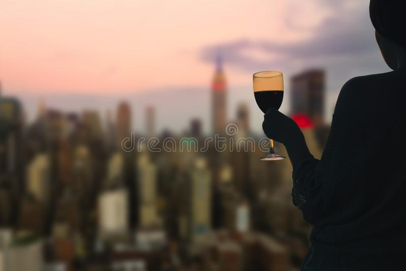 Female hand with glass of wine on Manhattan background. New York city. royalty free stock image