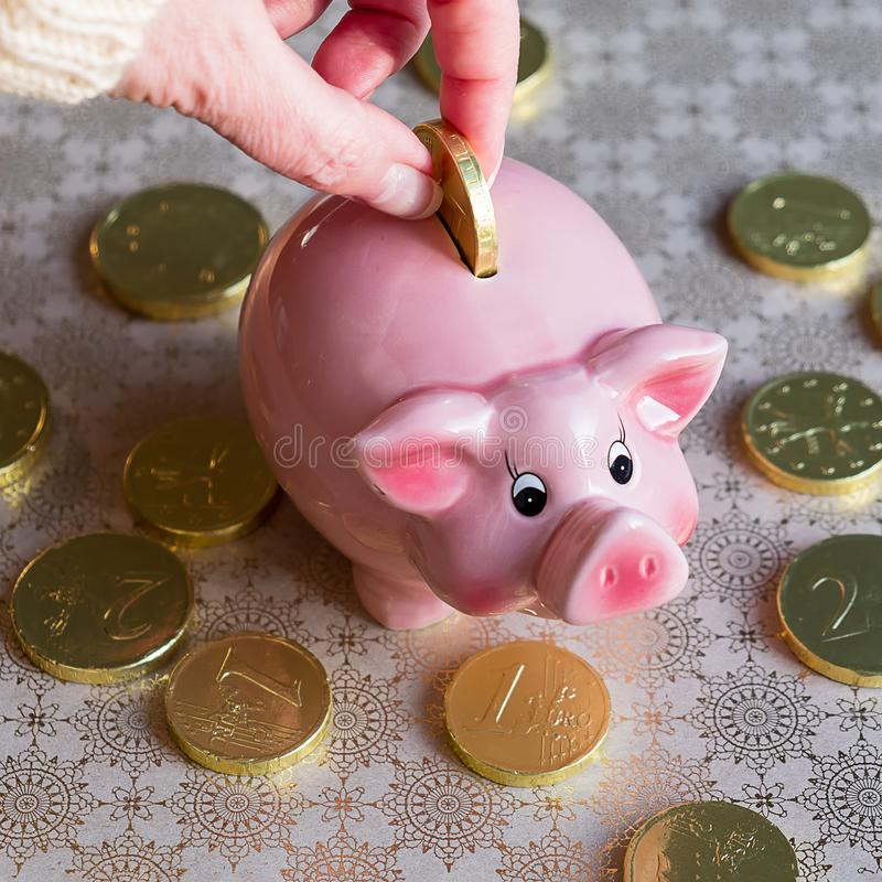 Female hand with gold chocolate coin and piggy bank stock photos