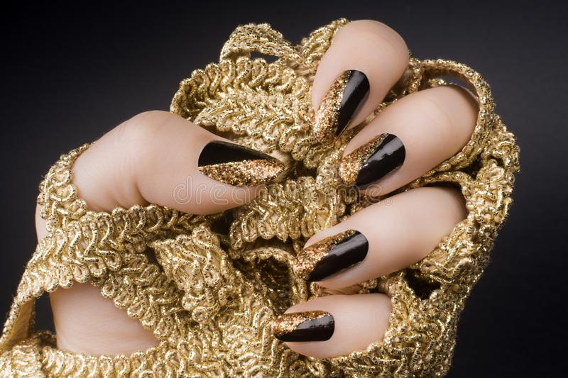 Golden black nails. Female hand with golden black nails is holding a golden decoration on black background stock images
