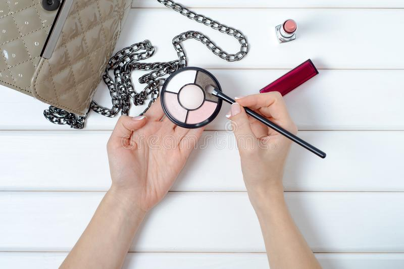 Female hand a handbag cosmetic eyeshadow. On a white wooden background royalty free stock image