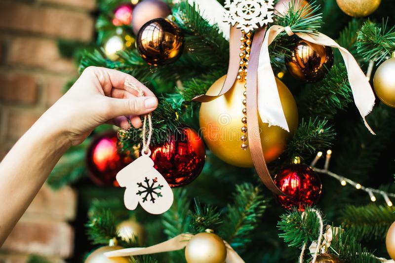 Female hand hangs on the Christmas tree wooden toy in the form of mittens. royalty free stock images