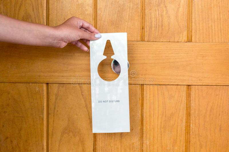 Female hand hangs a sign on the door do not disturb in hotel stock images