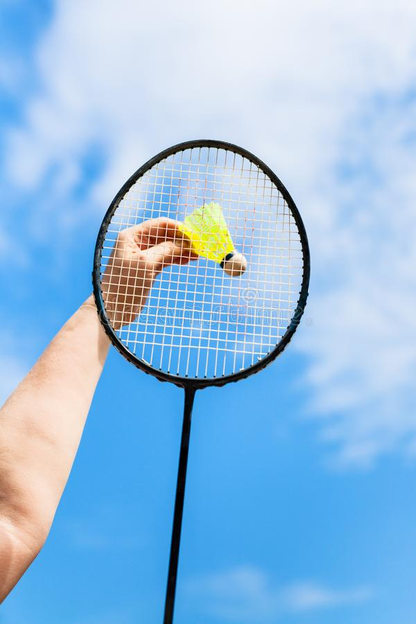 Female hand hits shuttlecock by badminton racquet royalty free stock image