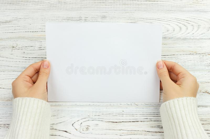A female hand hold an envelope and post card on the wood desk, top view Copy space stock photos