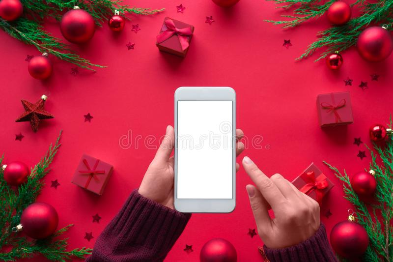 Female hands holding phone on merry Christmas red background, top view royalty free stock images