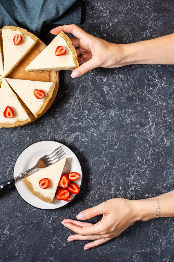 Female hand hold a slice of Homemade cheesecake with fresh strawberries on black stone background stock image