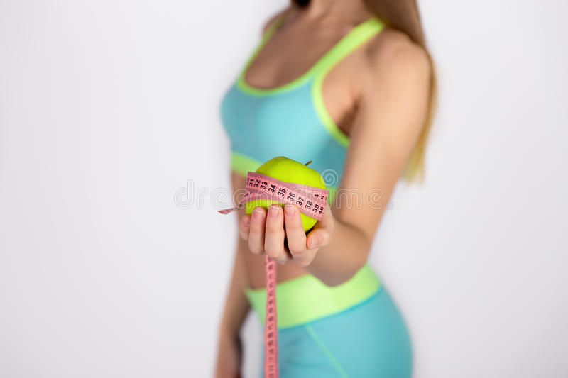 Female hand holding an apple and measuring tape royalty free stock photos