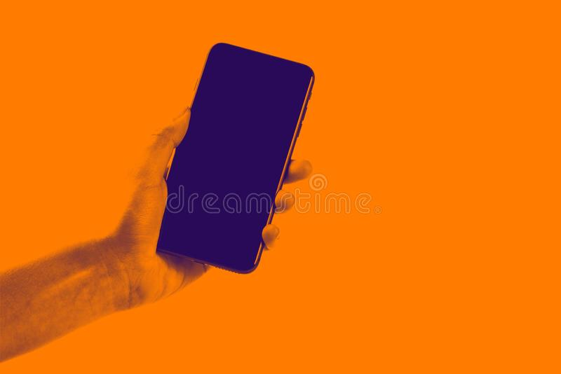 Female hand holding black cellphone with white screen at isolated background. royalty free stock image
