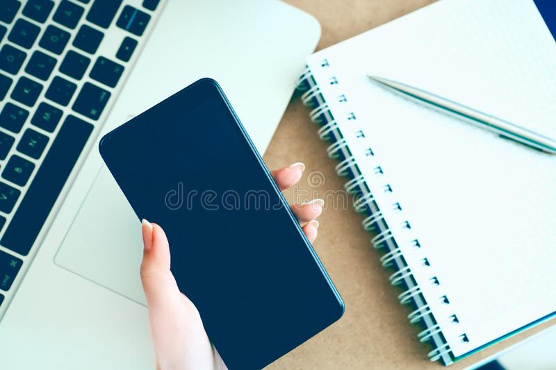 Female hand holding black mobile smart phone with blank screen on laptop computer and notepad background. Female hand holding black mobile smart phone with stock photo