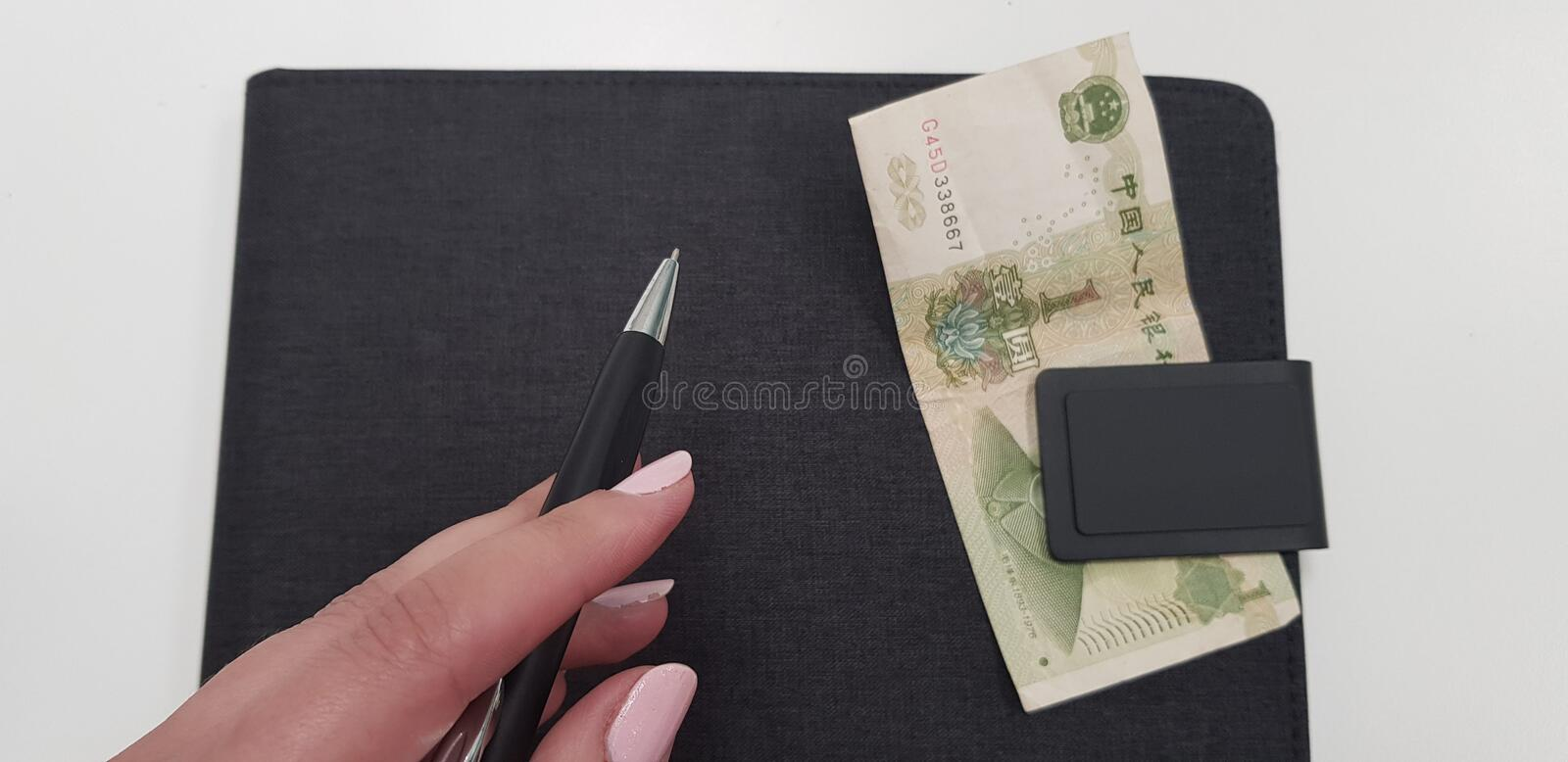 Female hand holding black pen on black folder. With one chinese money banknote bookmaker brokerage budget business china currency day earn economy education stock photography