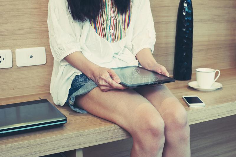 Female hand holding a black tablet computer while siting in the table with phone and laptop. modern lifestyle and business life royalty free stock photo