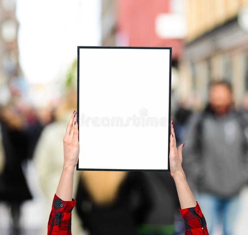 Female hand holding blank boards against city crowd - Woman rights concept stock images