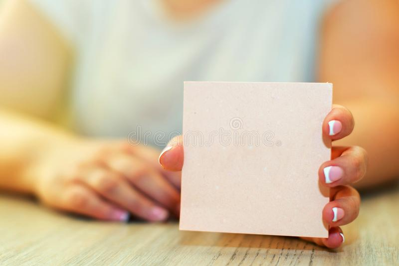 Female hand holding a blank paper card with copy space stock images