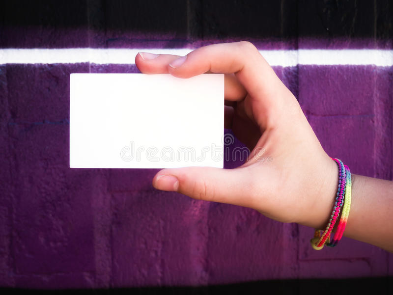 Female hand holding blank white business card. stock image