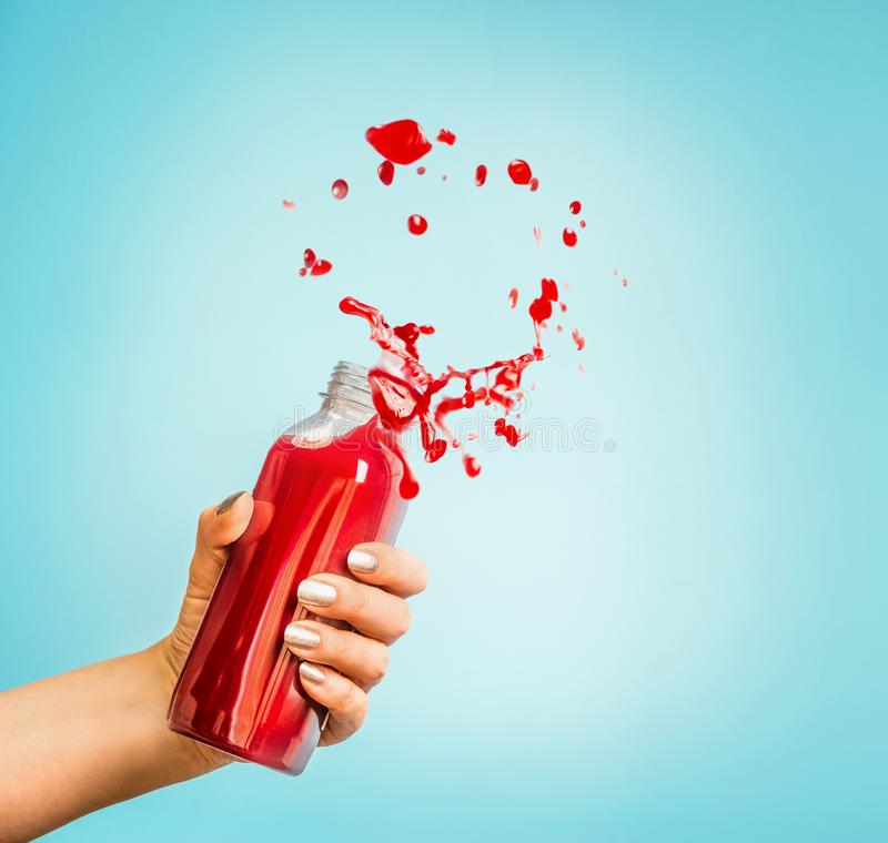 Female hand holding bottle with red splash summer beverage: smoothie or juice. At blue background stock photos