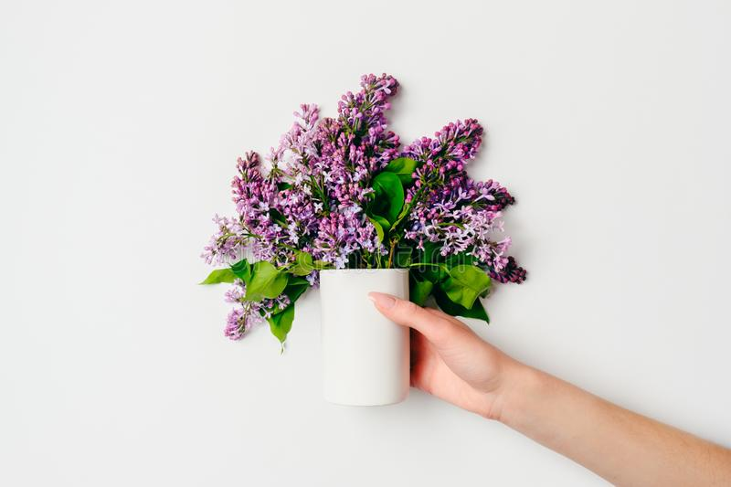 Female hand holding bouquet of lilacs flowers in modern glass vase on grey background. Flat lay composition in minimalist style, stock images