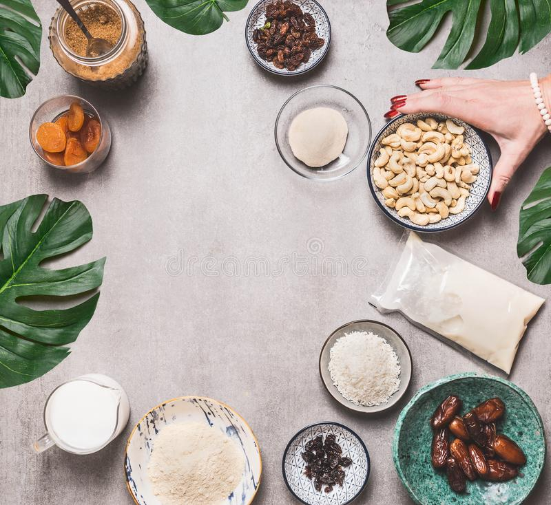 Female hand holding bowl with cashew on concrete background with vegan gluten-free cake ingredients: non dairy milk, almond flour. Coconut cream and milk, agar royalty free stock photo