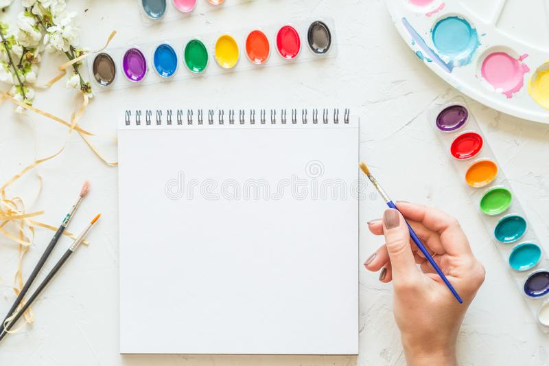 Female hand holding brush, nest lying watercolor and white notebook. Flat lay, top view. Place for text royalty free stock image