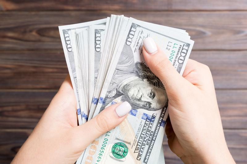Female hand holding a bundle of money on wooden background. Top view of one hundred dollar banknotes. Close-up of salary concept.  royalty free stock photo