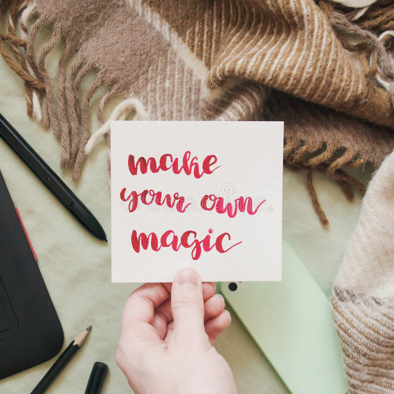 Female hand holding card with handwritten inspirational quote `make your own magic` stock images