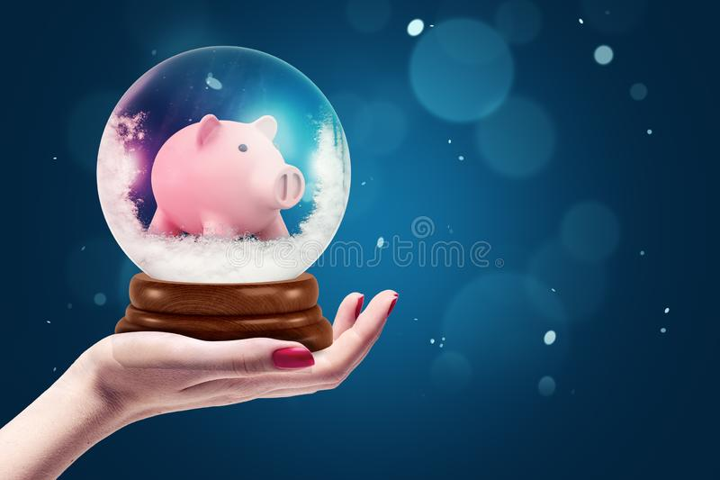 Female hand holding christmas snow globe with piggy bank inside on dark blue background. Home and decoration. Glass spheres. Christmas gifts royalty free stock photo