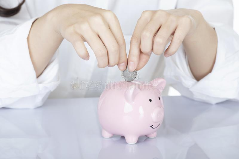 Female hand holding coins piggy bank , white background. Female hand holding Amicana coins and placing a quarter into a piggy bank  on white background royalty free stock images