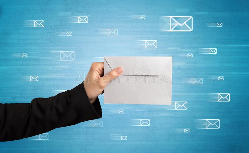 Hand holding envelope with message symbols around stock photography