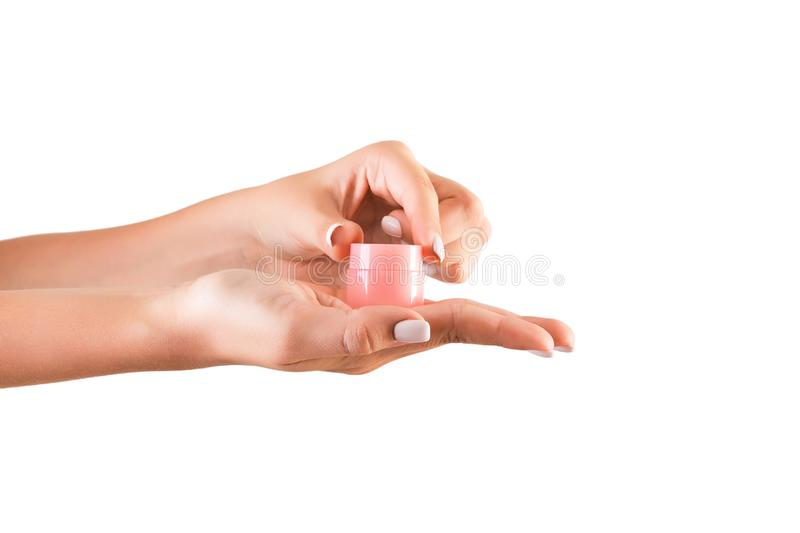 Female hand holding cream bottle of lotion isolated. Girl opening jar cosmetic products on white background stock photo