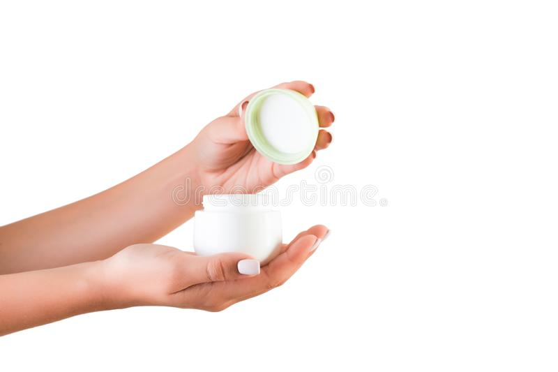 Female hand holding cream bottle of lotion isolated. Girl opening jar cosmetic products on white background.  stock photography