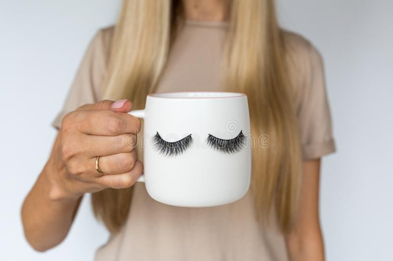Female hand holding cup with false eyelashes. Beauty and make up concept royalty free stock images