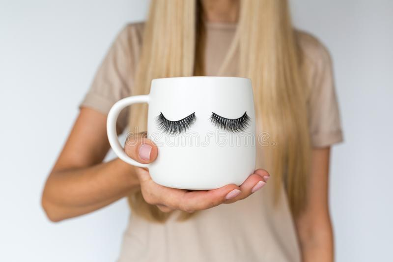 Female hand holding cup with false eyelashes. Beauty and make up concept royalty free stock photography