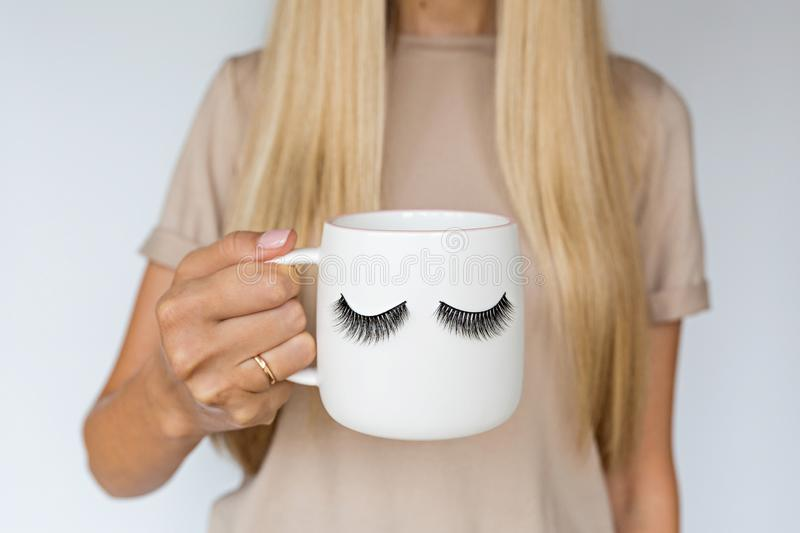 Female hand holding cup with false eyelashes. Beauty and make up concept royalty free stock image