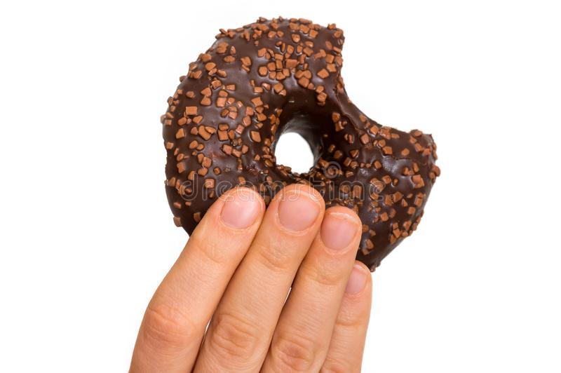 Female hand is holding donut with sprinkles royalty free stock photography