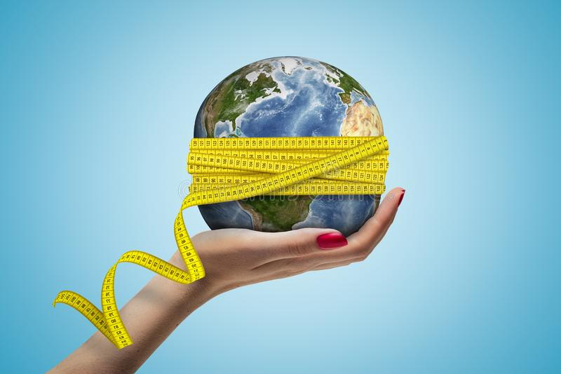 Female hand holding Earth globe covered with yellow measuring tape on blue background stock photos