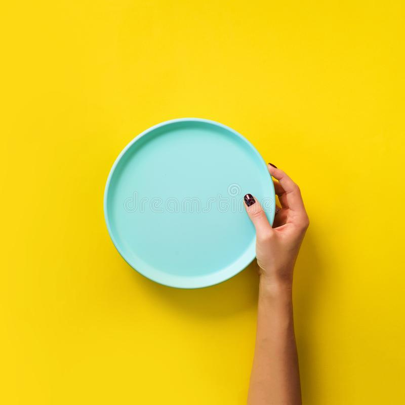 Female hand holding empty blue plate on yellow background with copy space. Healthy eating, dieting concept. Square crop stock image